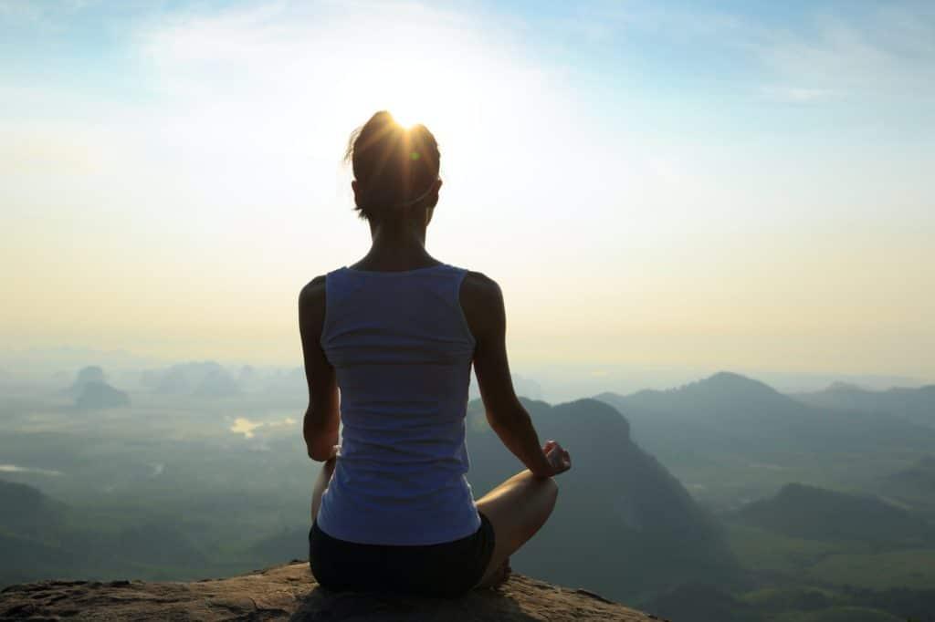Meditation bei Sonnenaufgang am Rande einer Bergklippe