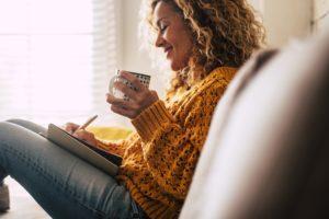 Glückliche niedliche Dame zu Hause schreiben Notizen auf ein Tagebuch, während eine Tasse Tee trinken und entspannen