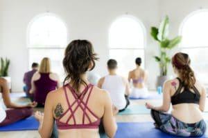 Healthy people making a Sukhasana yoga pose in yoga class