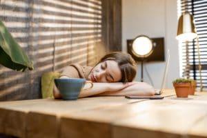 Verschlafene Frau am Arbeitsplatz zu Hause
